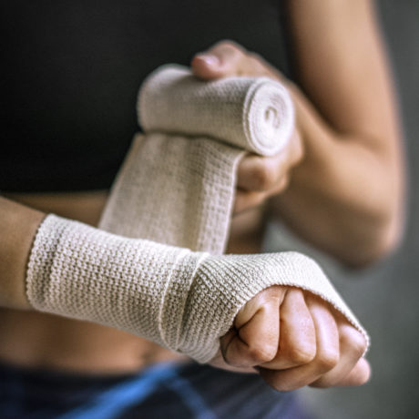 Female boxer putting a strap on her hand