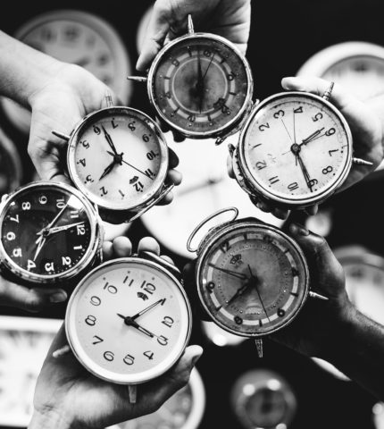 Closeup of hands holding clocks grayscale